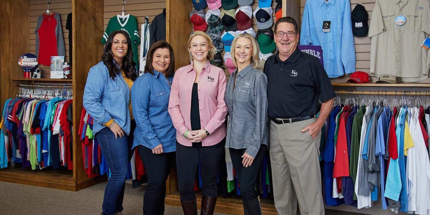 The team of K&S Sportswear standing in front of custom screen printing shirts, embroidered hats, and promotional products.